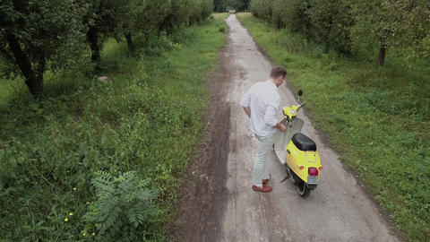 Young guy sits on a scooter on a country road. Shot on drone Footage