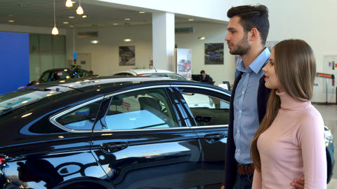Salesman gives the car key to the couple at the dealership Live Action