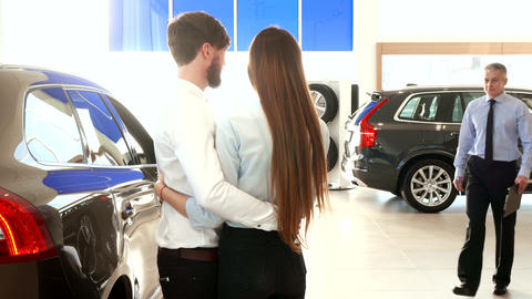 Salesman consults young couple at the car dealership Live Action