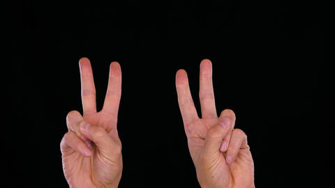 Two hand of man showing two fingers like quotes isolated on black background Live Action