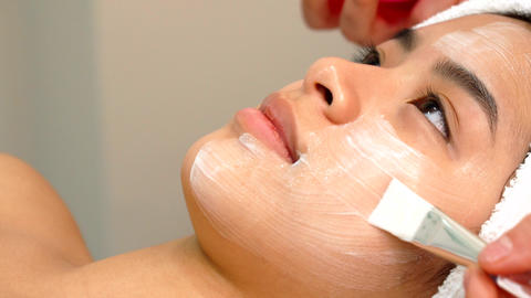 Beauty specialist uses brush to apply cosmetic mask on girl's face Live Action