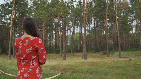Woman in red dress practice in shooting in forest Live Action