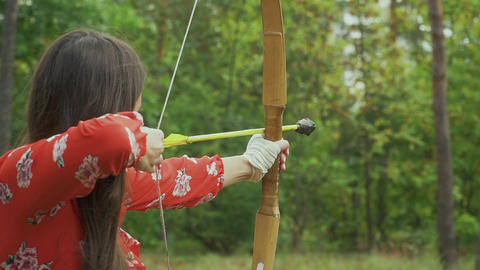 Beautiful girl aims and shoots with a bow. Close-up Live Action