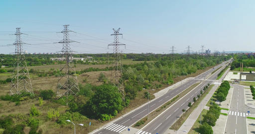 Power lines and road. Drone shot, flying backwards. Cars, bushes, low traffic Live Action