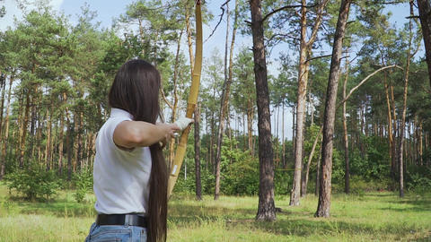 Female archer draving arrow and shooting target Live Action