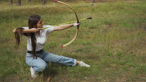 Girl shooting with bow from a sitting position Live Action