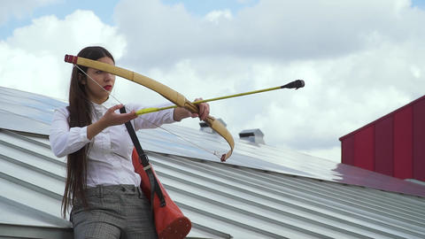 Young girl takes aim with a bow on the roof of a house Live Action