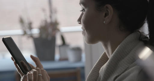 Close up browsing and texting on her phone by the window - 4K Live Action