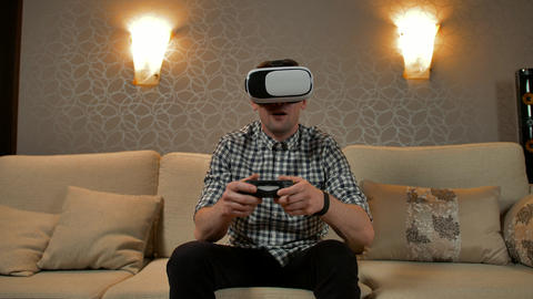 Young male wearing virtual reality headset playing game Live Action