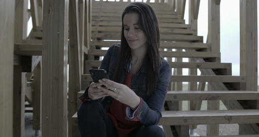 Woman browsing and texting on her phone outdoors by the stairs - 4K Live Action