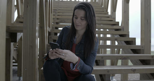 Woman browsing and texting on her phone outdoors by the... Stock Video Footage