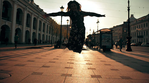 Happy cute girl jumping outdoor at city streets Footage
