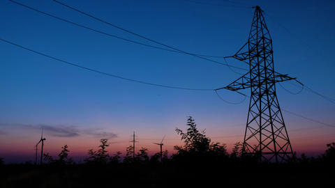 A silhouette of a power tower, standing against the last rays of setting sun ビデオ