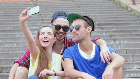 Cheerful girl sitting on the steps of his friends makes selfie Live Action