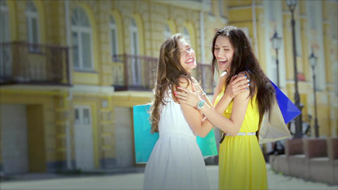 Two cute girls meet while shopping, a friendly hug and posing Footage