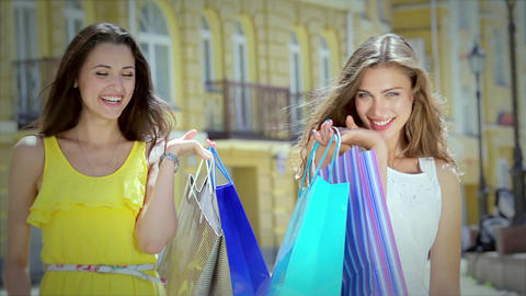 Two young glamorous girls go hand in hand with shopping bags Footage