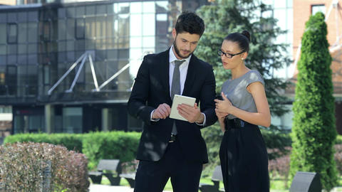 Business couple standing together, work on the tablet and smiling Footage