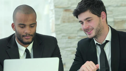 Two young men discussing information on the laptop screen Live Action