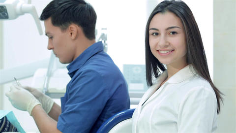 Girl-assistant smiling and thumb up on background dentist Live Action