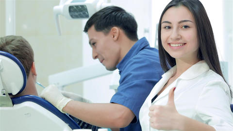 The dentist examines the teeth and smiles at him and the girl-assistant teeth Live Action