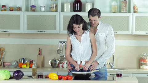 The girl chopped carrots, boy kissing a girl and add flavored oil in a frying Live Action
