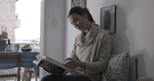 Woman reading at home next to the window - 4K Footage