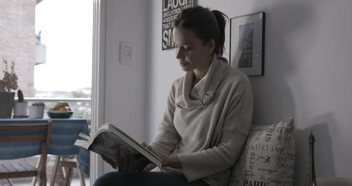 Woman reading at home next to the window - 4K Stock Video Footage