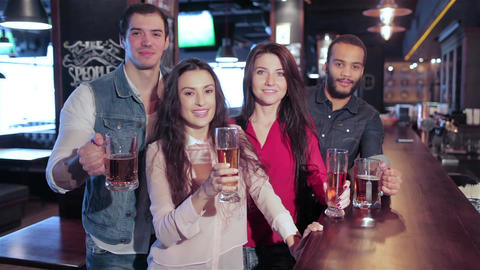 Four old friends at the bar with a glass of beer is welcomed new friends Live Action