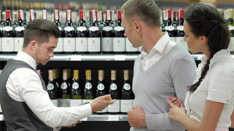 Salesman giving advice on buying bottle of wine Live Action