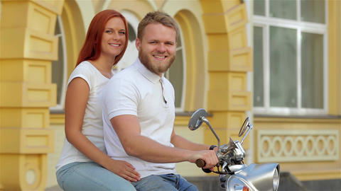 Glamorous couple riding a vintage scooter Footage