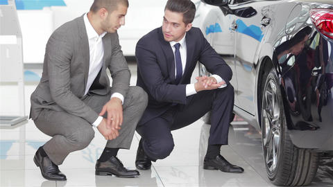 Salesman and customer in auto dealership Live Action