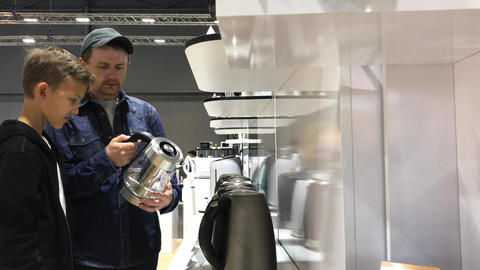 Father and son choose new electric kettle in shop ビデオ