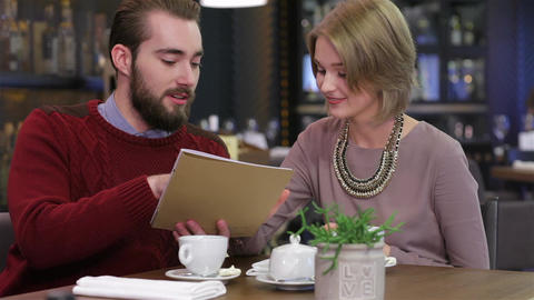 Smiling couple reading menu and choosing meal Footage
