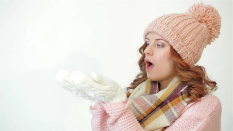 Girl with blue eyes holding and blowing snow Footage