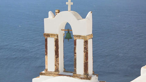 Old bell hanging in arch of rusty stand, view against blue sea, religion Greece Live Action