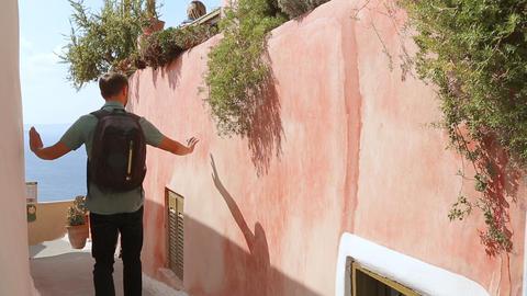 Male walking down narrow streets on sunny day on Santorini island Greece tourism Footage