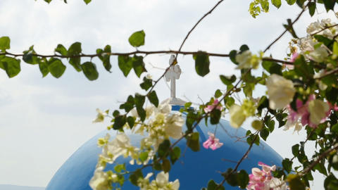 Cross standing on blue church dome, branches blooming in front, Greece tourism Footage