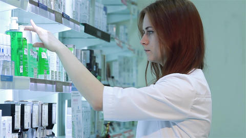 Pharmacist woman standing in pharmacy drugstore Footage