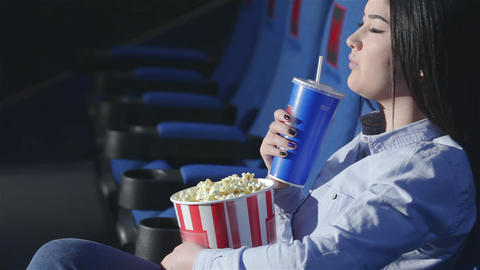 Asian girl in profile drinking soda in a cinema Footage