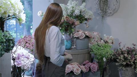 Female florist rearranges flowers at flower shop Footage