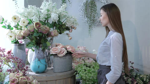 Female florist moving flowers near the window at flower shop Footage