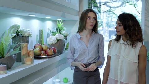 Two woman walk near flower shelf at flower shop Live Action