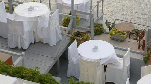 Dining tables standing on terrace over sea, eating in seaside restaurant, resort Live Action