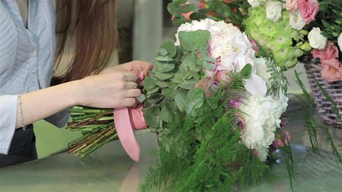 Female florist makes a bouquet of flowers at flower shop Stock Video Footage