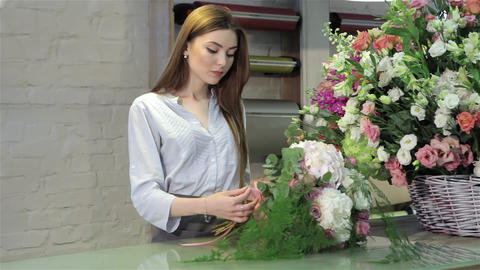 Female florist demonstrate a bouquet of white flowers at flower shop Footage