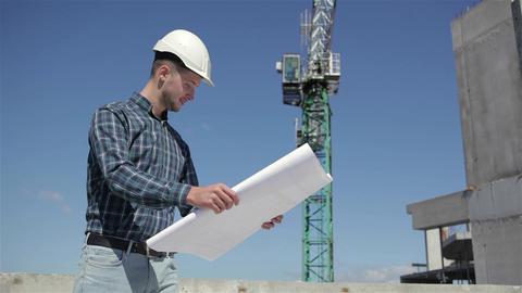 Construction manager look at the sheet with plan of building under construction Footage