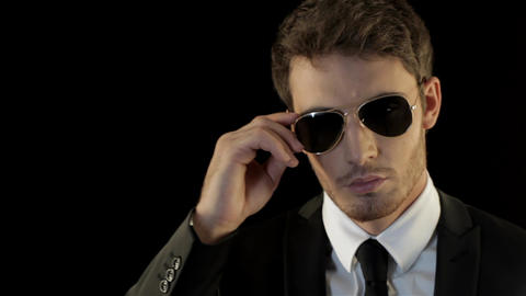 Man looks over his sunglasses like special agent Live Action