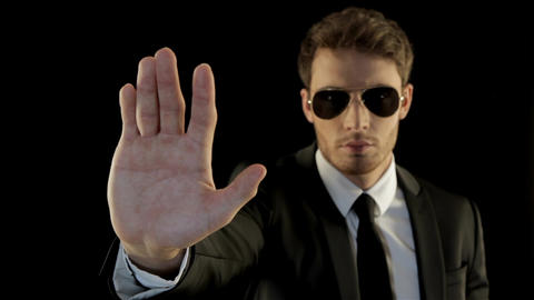 Man in black gestures stop like security service Live Action