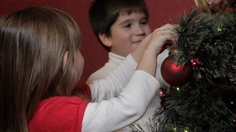 Little boy hangs decorating bow on christmas tree Live Action