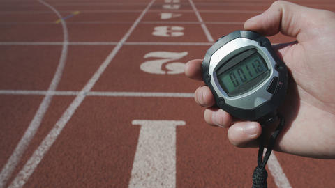 Male hand turning on stopwatch to record time during sport competition, deadline Live Action